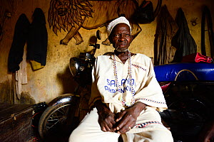 Voodoo healer / azeto of Djenan Temple, motorbike and mural of lion in background. Abomey, Benin, 2020.  -  Enrique Lopez-Tapia