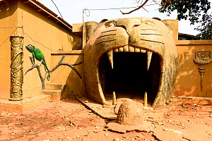 Great voodoo temple, cat or tiger sculpture surrounding an entrance with a chameleon mural on wall. Abomey, Benin, 2020.  -  Enrique Lopez-Tapia