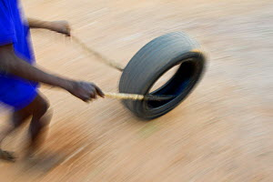 Somba boy playing, rolling a car tyre. Benin, 2020.  -  Enrique Lopez-Tapia