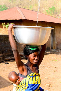 Woman carrying baby on back collecting water from fountain, dish balanced on her head. Dassa, Benin, 2020.  -  Enrique Lopez-Tapia