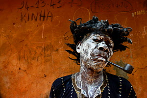 A man represents a sick and smoking character, in a voodoo ceremony in the village of Bohicon, Benin. January 2020  -  Enrique Lopez-Tapia