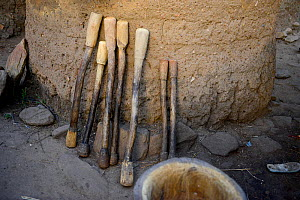 Wooden tools lined up against traditional clay barn, tools used to grind yams. Taneka community. Benin, 2020.  -  Enrique Lopez-Tapia