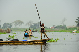Tofinou boy transporting plastic containers in boat on Lake Nokoue, Oueme River Delta. Ganvie, known as African Venice, Benin, 2020.  -  Enrique Lopez-Tapia