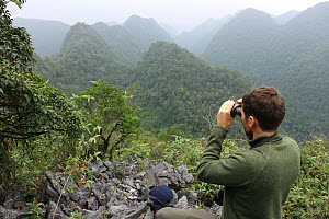 Fauna & Flora International staff member using binoculars to monitor gibbon activity. Cao vit gibbon Species & Habitat Conservation Area, Trung Khanh district, Cao Bang province, Vietnam. EDITORIAL US...  -  Nguyen Duc Tho / Fauna & Flora International