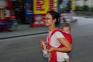 Woman out shopping with baby on back, Mother and baby out shopping and walking in the street, Old Julong village, Guangzhou, Guangdong, China November 2015.  -  Staffan Widstrand / Wild Wonders of China