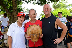 Man holding Horseshoe crab (Tachypleus tridentatus) at Horseshoe crab release event oragnized by Ocean Park Conservation Foundation, Hak Pak Nai beach, Yue Long, Hong Kong, China  -  Wayne Wu Ying / Wild Wonders of China
