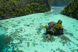 Lagoon between forested karst islands, tourists paddleboarding and canoeing, aerial view. Raja Ampat Islands, West Pappua, Indonesia. 2018.  -  Juergen Freund