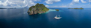 Phinisi dive boat amongst karst limestone islands, aerial view. Raja Ampat Islands, West Papua, Indonesia. 2018.  -  Juergen Freund