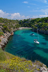 Yachts moored in the cove at Cala Pi, viewed from narrow cliff top coast path, Mallorca south coast, August 2018.  -  Nick Upton