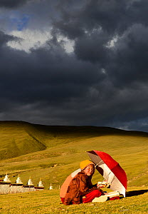 Buddhist novices studying and reciting mantra, outdoors in steppe under stormy sky. Ganden Thubchen Choekhorling Monastery, Litang, Garze Tibetan Autonomous Prefecture, Sichuan, China. October 2016.  -  Enrique Lopez-Tapia