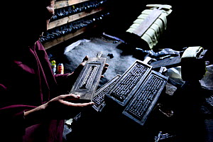 Monk with wooden plates used to print Buddhist prayers and texts. Palpung Monastery, Kham, Dege County, Garze Tibetan Autonomous Prefecture, Sichuan, China. 2016.  -  Enrique Lopez-Tapia