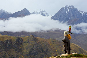 Man on Buddhist pilgrimage standing, looking out over mountains. Kham, Tibet. October 2016.  -  Enrique Lopez-Tapia