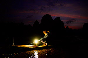 Traditional Chinese fisherman on raft on Li River at dusk, Karst peaks silhouetted in background. Yangshuo, Guangxi, China. 2016.  -  Enrique Lopez-Tapia