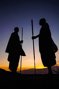 Masaai warriors, two silhouetted in ceremonial dance at dusk. Ngorongoro Conservation Area, Serengeti National Park, Tanzania. March 2014.  -  Nick Garbutt