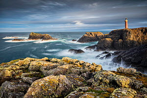 Butt of Lewis lighthouse viewed across rocky cliffs and sea, in stormy light. Isle of Lewis, Outer Hebrides, Scotland, UK. November 2016.  -  Guy Edwardes