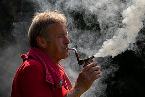 Beekeeper Winfried Jordan blowing a lot of smoke with his traditional bee smoker, an important equipment of a beekeeper to calm down honey bees (Apis mellifera), Germany.  -  Ingo Arndt