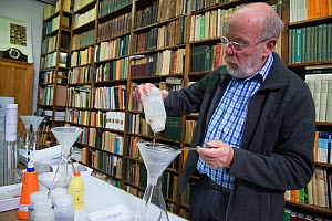 Entomologist draining Insect sample prior to weighing, reference books in background. Long-term monitoring has revealed a 75% decline in insect biomass over 27 years. Entomological Society Krefeld, Ge...  -  Edwin Giesbers