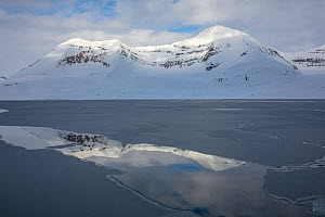 Snow covered mountains on fjord reflected in crack in ice. Hornsund, Svalbard, Norway. May 2018.  -  Pal Hermansen