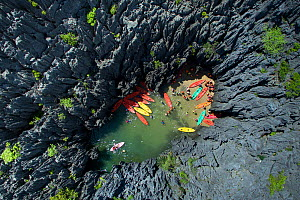 Group of tourists with colourful kayaks entering a small beach surrounded by jagged karst formation of Prasat Hin Phanyod. An ecotourism destination managed by local community in Mu Koh Phetra Nationa...  -  Sirachai Arunrugstichai