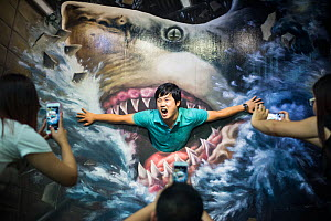 Tourist poses for a photo shoot with image of a Great white shark (Carcharodon carcharias) at Phuket Trickeye Museum, Phuket Province, Thailand, December 2015  -  Sirachai Arunrugstichai