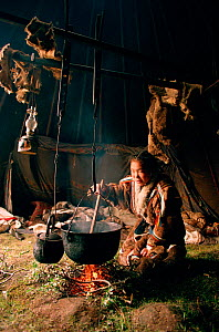 Valya Serotetto, a Nenets girl, stirs a pot of reindeer stew over an open fire in a tent. Yamal. Siberia. Russia.1993.  -  Bryan and Cherry Alexander