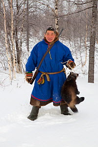 Leova Serotetto, a Nenets reindeer herder, holds a dead wolverine that he shot near his family's reindeer herd. Yamal, NW Siberia, Russia. 2017.  -  Bryan and Cherry Alexander