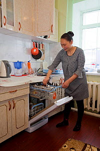 Valya Khudi,a Nenets woman, unloading the dish washer in the modern kitchen of her family's apartment in Yar-Sale, Yamal, NW Siberia, Russia. 2017.  -  Bryan and Cherry Alexander