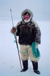 Ituko, an Inuit hunter, dressed in fox parka and polar bear fur trousers, holding a harpoon. N.W. Greenland. 1980.  -  Bryan and Cherry Alexander