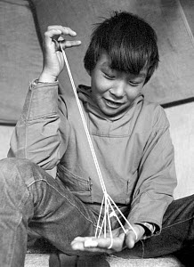 Magssanguak Imina making a traditional string puzzle that represents a tent, while sitting in a tent. Thule, Northwest Greenland. 1971  -  Bryan and Cherry Alexander