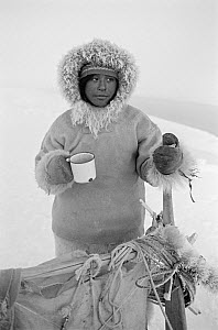 Otto Simigak with a mug of tea during a break on a hunting trip in light snow. Siorapaluk, Northwest Greenland.1977.  -  Bryan and Cherry Alexander