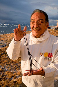 Magssanguaq Imina, an Inuit man from Qaanaaq, demonstrates a traditional string puzzle called the tent. He is wearing a white anorak which he wears on Sundays and celebratory occasions. Avanersuaq, No...  -  Bryan and Cherry Alexander