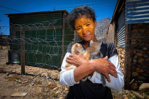 A woman selling kittens to buy food, De Doorns, South Africa. November 2018. The woman's cat had just given birth. The yellow face paint she is wearing acts as sunscreen.  -  Aaron Gekoski