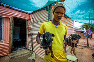 A man holding two pet puppies, De Doorns, South Africa. February 2018. The yellow face paint acts as sunscreen.  -  Aaron Gekoski