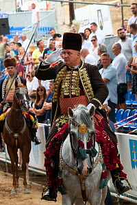 Man on horseback saluting during Alka procession, spectators in background. Held on the first Sunday in August since 1715 the Alka commemorates the victory of Christians over Ottoman Turks. Inscribed...  -  Kristel Richard