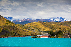Pehoe Lodge on shore of Lake Pehoe, mountains beyond. Lake turquoise coloured due to glacial rock flour. Torres del Paine National Park, Patagonia, Chile. January 2020.  -  Ashley Cooper
