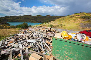 Skip and pile of rubbish from a tourist lodge, Lake Pehoe in background. Torres del Paine National Park, Patagonia, Chile. January 2020.  -  Ashley Cooper
