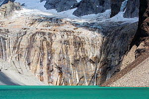 Meltwater from retreating glacier flowing over rock into lake, below Torres del Paine towers. Torres del Paine National Park, Patagonia, Chile. January 2020.  -  Ashley Cooper
