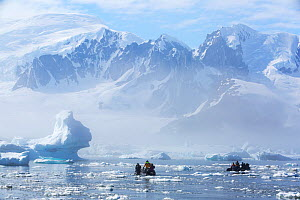 Zodiacs with tourists from expedition cruise ship in Southern Ocean around Yalour Islands, snow covered mountains in background. Wilhelm Archipelago, Antarctica. January 2020.  -  Ashley Cooper