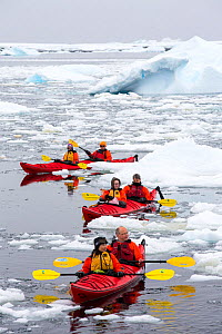 Tourists from expedition cruise ship sea kayaking amongst sea ice and icebergs. Off Vernadsky Station, Galindez Island, Antarctica. January 2020.  -  Ashley Cooper