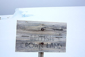 Fading wooden sign reading 'British Crown Land' outside Wordie House, a former British scientific research base. Winter Island, Argentine Islands, Antarctica. January 2020.  -  Ashley Cooper