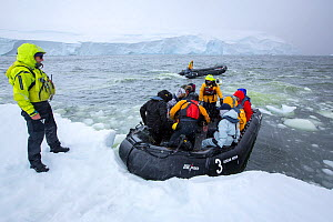 Tourists from expedition cruise ship in zodiac at edge of sea ice. Lallemand Fjord, an area formerly covered by the Muller ice shelf which collapsed due to climate change. Antarctica. January 2020.  -  Ashley Cooper