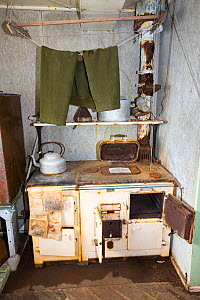 Trousers drying above kitchen stove, Station W, former British scientific research station evacuated in 1959. Detaille Island, Graham Land, Antarctica. 2020.  -  Ashley Cooper