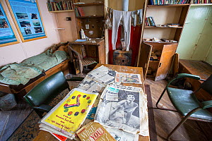 Magazines on table and clothes drying over stove in Station W, a former British scientific research station evacuated in 1959. Detaille Island, Graham Land, Antarctica. 2020.  -  Ashley Cooper