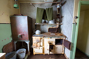 Trousers drying above kitchen stove, as left when researchers were evacuated in 1959. Station W, former British scientific research station, Detaille Island, Graham Land, Antarctica. 2020.  -  Ashley Cooper