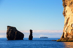 Coastal cliff and sea stack in Southern Ocean with cruise ship in background. Deception Island, South Shetland Islands, Antarctica. December 2019.  -  Ashley Cooper