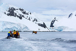 Tourists from expedition cruise ship in zodiacs heading towards mountains of Spert Island, Palmer Achipelago, Antarctica. December 2019.  -  Ashley Cooper