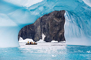 Tourists from expedition cruise ship in zodiac between ice arch and rock cliff on Spert Island. Palmer Archipelago, Antarctica. December 2019.  -  Ashley Cooper