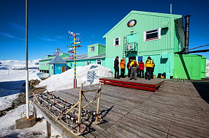 Tourists from expedition cruise ship visiting Vernadsky Station Ukrainian research base, dog sleds in foreground. Galindez Island, Argentine Islands, Antarctica. December 2019.  -  Ashley Cooper