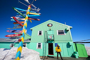 Man outside Vernadsky Station Ukrainian research base, signpost pointing to places across the world. Galindez Island, Argentine Islands, Antarctica. December 2019.  -  Ashley Cooper