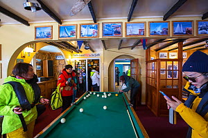 Tourists from expedition cruise ship playing at billiards table and purchasing postcards in shop. Vernadsky Station Ukranian research base, Galindez Island, Argentine Islands, Antarctica. 2019.  -  Ashley Cooper
